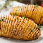 Hasselback potatoes with herbs on a plate