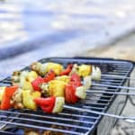 Chicken skewers cooking on portable grill at the beach