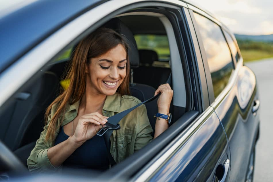 Young attractive woman sitting on car seat and fastening seat belt,